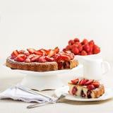 Hemlagad jordgubbekaka på en ställning för vit kaka royaltyfri bild