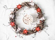 Hemlagad julvinrankakrans med röda trästjärnor och varm choklad med marshmallower på vit bakgrund, bästa sikt kopiera avstånd arkivfoton