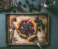 Hemlagad körsbärsröd paj eller galette på den åldriga bakplåten och lantlig köksbordbakgrund med driftstopp och bestick, bästa si arkivfoto