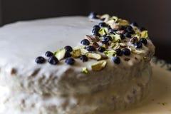 Hemlagad kaka med vit buttery kräm med prydnaden från den blåbärbär och pistaschen på en mörk bakgrund royaltyfria foton