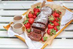 Hemlagad kaka och nya jordgubbar på en vit trädgårdbänk royaltyfri foto