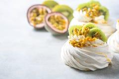 Hemlagad kaka Pavlova med piskad kräm, den nya kiwin och passionfrukt Royaltyfria Bilder