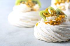 Hemlagad kaka Pavlova med piskad kräm, den nya kiwin och passionfrukt Arkivbild