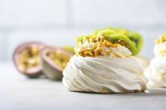 Hemlagad kaka Pavlova med piskad kräm, den nya kiwin och passionfrukt Royaltyfria Foton