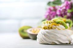 Hemlagad kaka Pavlova med piskad kräm, den nya kiwin och passionfrukt Royaltyfri Foto