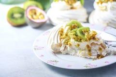 Hemlagad kaka Pavlova med piskad kräm, den nya kiwin och passionfrukt Royaltyfri Bild