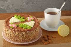 Hemlagad Kiev kaka, kopp te och spridda mandlar arkivfoto