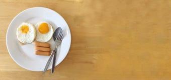Hemlagad läcker amerikansk frukost med den soliga sidan upp det stekte ägget och korvar i den vita maträttserven med orange frukt royaltyfria foton