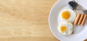 Hemlagad läcker amerikansk frukost med den soliga sidan upp det stekte ägget och korvar i den vita maträttserven med orange frukt royaltyfria bilder