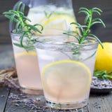 Hemlagad lemonad med lavendel, nya citroner och rosmarin på en träbakgrund, fyrkantigt format Royaltyfri Foto