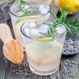 Hemlagad lemonad med lavendel, nya citroner och rosmarin på träbakgrund, fyrkantigt format Royaltyfria Bilder