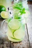 Hemlagad lemonad med limefrukt, mintkaramell i en murarekrus på en trätabell arkivfoton