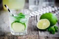 Hemlagad lemonad med limefrukt, mintkaramellen och is på en trätabell royaltyfri fotografi