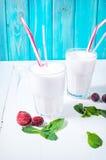 Hemlagad milkshake med mintkaramellen och bäret på den vita trätabellen arkivfoton