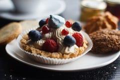 Hemlagad muffin med kräm- och nya bär för blåbär, på träbakgrund Royaltyfria Bilder