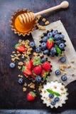 Hemlagad mysligranola och yoghurt med bär på den rostiga tabellen Royaltyfri Fotografi