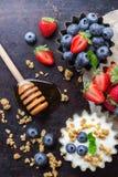 Hemlagad mysligranola och yoghurt med bär på den rostiga tabellen Arkivbilder