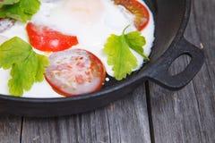 Hemlagad omelett i en stekpanna Äggfrukost med tomaten och PA Royaltyfria Bilder