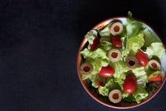 Hemlagad organisk grönsallatsallad med tomaten och oliv Arkivbild