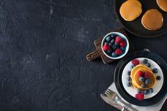 Hemlagad pannkakabunt med bär över svart textur Royaltyfri Fotografi