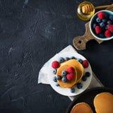Hemlagad pannkakabunt med bär över svart textur Arkivfoton