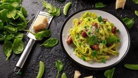 Hemlagad pasta med gröna ärtor, spenatpesto och korvar Parmesanost Isolerat på vit bakgrund sund mat arkivbild