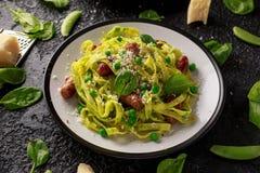 Hemlagad pasta med gröna ärtor, spenatpesto och korvar Parmesanost Isolerat på vit bakgrund sund mat royaltyfria bilder