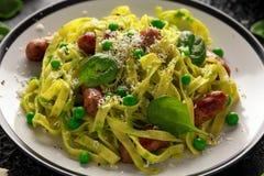Hemlagad pasta med gröna ärtor, spenatpesto och korvar Parmesanost Isolerat på vit bakgrund sund mat close upp royaltyfri foto