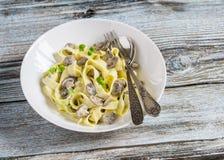 Hemlagad pasta med krämig champinjonsås på en ljus träbakgrund Royaltyfria Bilder