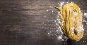 Hemlagad pasta med mjöl på den övre gränsen för trälantligt för bakgrund slut för bästa sikt, ställe för text Royaltyfria Bilder