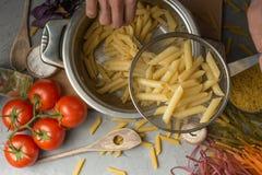 Hemlagad pasta som lagar mat i en kruka av vatten och lagar mat ingredienser med en skärbräda, bästa sikt Det begreppet av italie arkivbilder