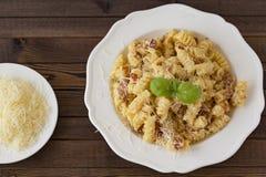 Hemlagad pastacarbonaraitalienare med bacon, ägg, parmesanost på den vita plattan på en mörk bakgrund arkivbild