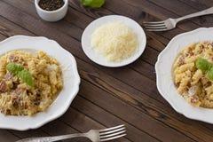 Hemlagad pastacarbonaraitalienare med bacon, ägg, parmesanost på den vita plattan på en mörk bakgrund fotografering för bildbyråer