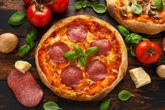 Hemlagad peperoni, salami, champinjonpizza med basilika, tomater, ost på trätabellen ordna till f?r att ?ta arkivbilder