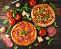 Hemlagad peperoni, salami, champinjonpizza med basilika, tomater, ost på trätabellen ordna till f?r att ?ta arkivfoto