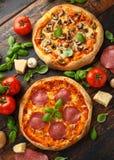 Hemlagad peperoni, salami, champinjonpizza med basilika, tomater, ost på trätabellen ordna till f?r att ?ta arkivfoton