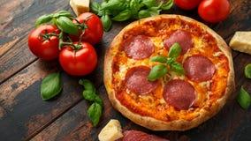 Hemlagad peperoni, salamipizza med basilika, tomater, ost på trätabellen ordna till f?r att ?ta royaltyfria bilder