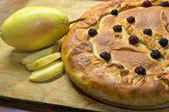 hemlagad pie för äpple Baka ihop med stycken av äpplen och ett päron på ett träbräde close upp fotografering för bildbyråer