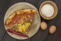 hemlagad pizza Delar av pizza på en mörk trätabell Royaltyfri Fotografi