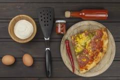 hemlagad pizza Delar av pizza på en mörk trätabell Arkivfoto