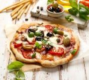 Hemlagad pizza med tomater, oliv, salami, mozzarellaost och ny basilika på en trälantlig tabell Arkivbilder