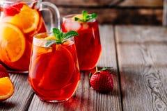 Hemlagad rött vinsangria med apelsinen, äpplet, jordgubben och is i exponeringsglas och kanna på träbakgrund Fotografering för Bildbyråer