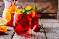Hemlagad rött vinsangria med apelsinen, äpplet, jordgubben och is i exponeringsglas och kanna på träbakgrund Royaltyfri Fotografi
