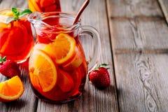 Hemlagad rött vinsangria med apelsinen, äpplet, jordgubben och is i kanna och exponeringsglas på träbakgrund Royaltyfria Bilder
