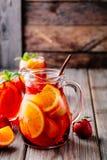 Hemlagad rött vinsangria med apelsinen, äpplet, jordgubben och is i kanna och exponeringsglas på träbakgrund Royaltyfri Foto