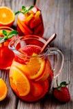 Hemlagad rött vinsangria med apelsinen, äpplet, jordgubben och is i kanna och exponeringsglas på träbakgrund Royaltyfria Foton