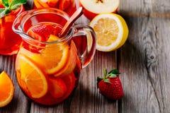 Hemlagad rött vinsangria med apelsinen, äpplet, jordgubben och is i kanna och exponeringsglas på träbakgrund Arkivfoton