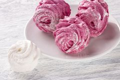 Hemlagad rosa och vit marshmallow på en platta på en gammal trätabellnärbild royaltyfri bild