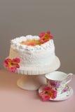 Hemlagad söt paj med dekorerade naturliga blommor för vit kräm på rosa färgtabellen vertikalt Royaltyfria Foton