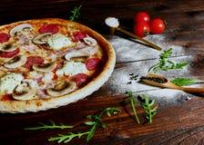 Hemlagad skinka-, salami- och champinjonpizza tjänade som på ett bräde på ett gammalt lantligt träköksbord som omgavs av det nytt arkivfoto